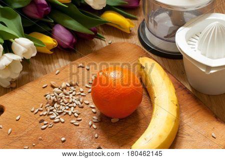 Banana, Orange And Seeds Vivid Smoothie Ingredients And Blender, Juicer, Tulips On The Background