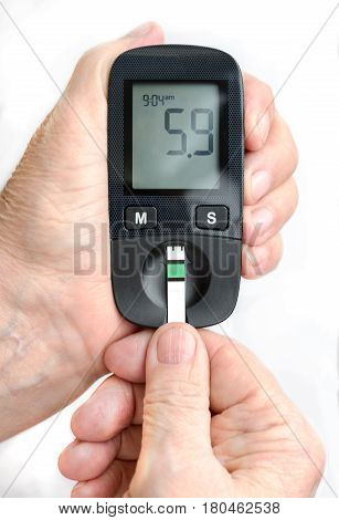 An elderly woman holds a glucometer in her hands and wants to do a blood test for sugar