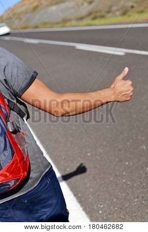 closeup of a young caucasian man seen from behind carrying a backpack hitchhiking in a minor road, with his thumb up