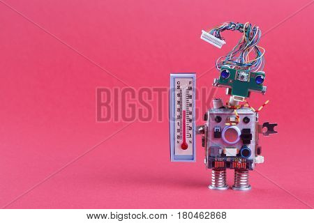 Weather forecasting concept photo. Robot weathermen with thermometer displaying comfort room temperature 21 degree celsius. Funny head robotic toy character on pink background, copy space.