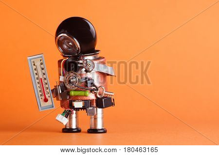 Weather forecaster robot looking thermometer comfort room temperature 21 degree celsius. Weathermen toy character with black helmet head on orange background, copy space.