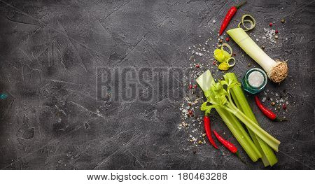 Vegetable Ingredients red hot pepper red white and black pepper shallots and celery on a black background. Top view with place for text
