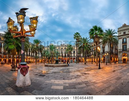 BARCELONA SPAIN - NOVEMBER 17 2014: Placa Reial in Barcelona Spain. The square with lanterns designed by Gaudi and the Fountain of Three Graces in the center.