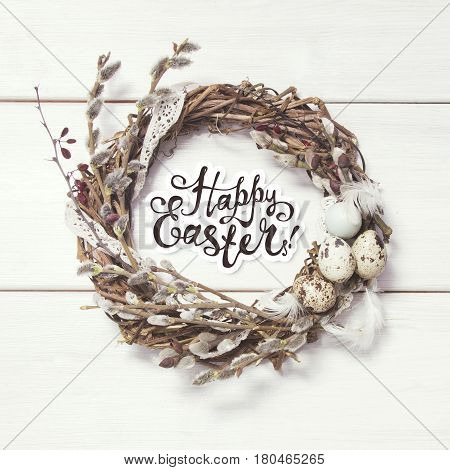 Happy Easter card. Wreath with willow twigs and quail eggs on white wooden background