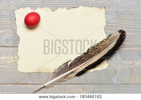 Red Easter Egg With Writing Feather And Paper On Wood