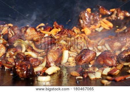 Hot cook meat onion carrot vegetable in smoke fry on cauldron pan. The stage of cooking pilaf