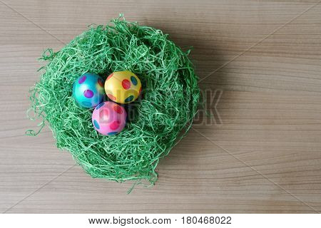 top view of three dotted easter eggs in a nest made from artificial grass decoration on table with copy space