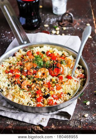 Couscous warm salad with red sweet bell pepper, eggplant, courgette, cherry tomatoes, roasted shrimps and dill in a pan, selective focus