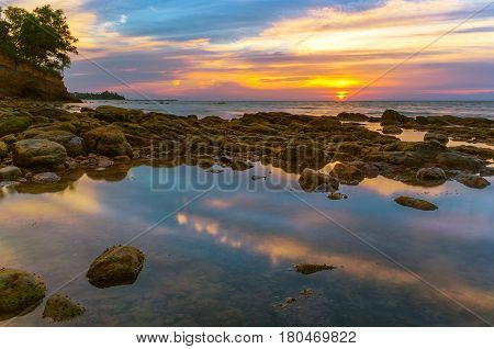 Low tide on Labuan Island at beautiful sunset with reflection of clouds with beach stones.Copy space.