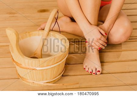Closeup of human woman legs feet hands with sauna bucket and ladle. Person relaxing resting in spa.