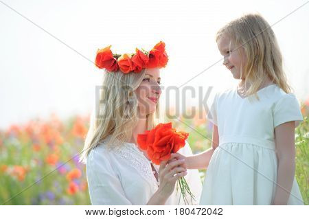 child giver flowers to his mom. Outdoors family portrait daughter with mother