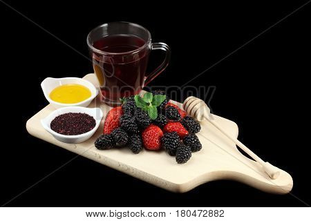 Forest fruits on a cutting board. Tea made of forest fruits with natural honey