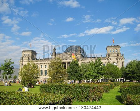 Reichstag, Deutscher Bundestag building, headquarter of German Parliament, in Berlin, Germany. View from local park summer colorful scene with green grass trees blue sky empty background