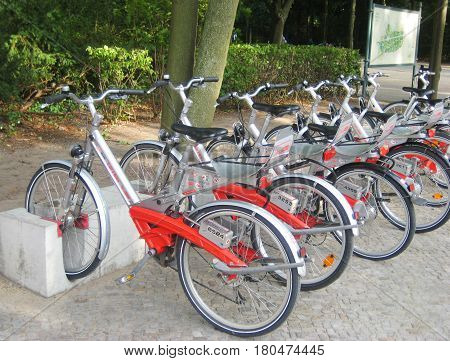 BERLIN, GERMANY - JULY 20, 2016: Bikes parked and lined up in the streets of downtown Berlin - city center bike renting service for tourists and locals easy transportation through the city