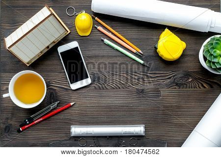 Architects workplace with constructor tools with cup of tea and mobile on wooden table background top view