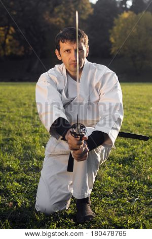 Ninja in white kimono with sword is practicing martial arts outdoors.
