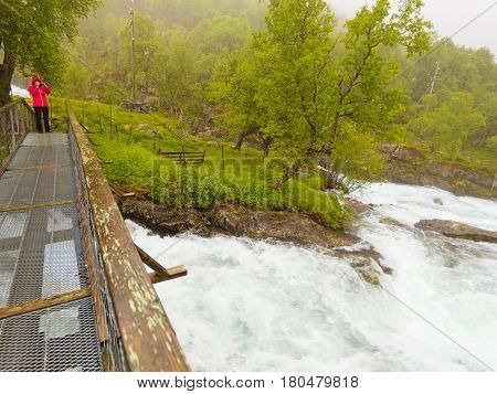 Travel and hiking. Tourist woman taking photo with camera standing on bridge enjoying waterfall torrential river along the Aurlandsfjellet mountains in Norway Sogn og Fjordane foggy hazy summer day