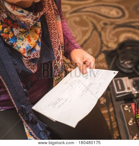 Woman holding paper with lyrics and notes while recording in a studio. Guitar equipment nearby.