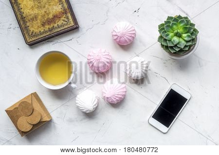 trendy office desk of woman with marsh-mallow and mobile on light wooden background top view space for text