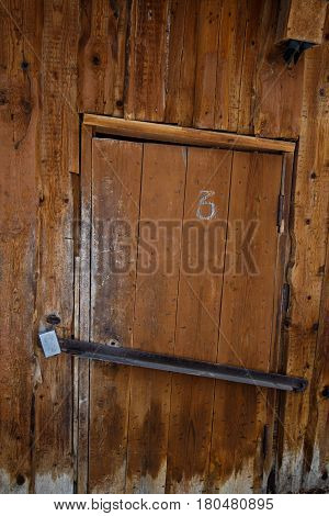 Wooden Door Of An Old Barn With A Metal Lock