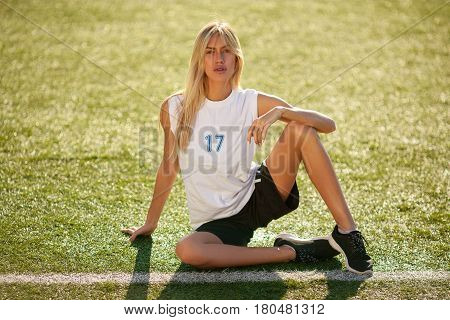 Girl In Soccer Uniform  Sitting On Football Field.