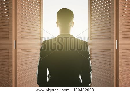 Back view of young businessman looking at bright light shining from open brown doors. Success concept. 3D Rendering