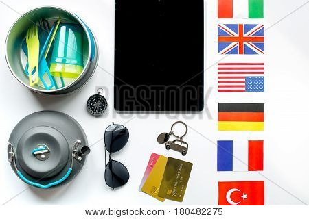 traveller lifestyle items with credit cards and tablet on white table background top view