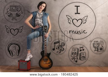 Attractive young female with guitar and foot on amplifier standing in interior with sketch on concrete wall. Music concept