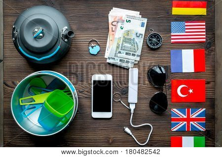 traveller lifestyle items with compass and plactic dishes on wooden table background top view