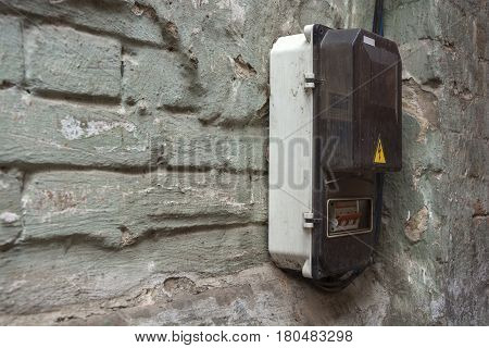 The electrical shield mounted in the corner of a brick wall