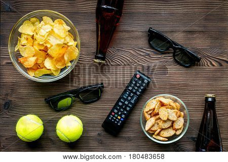 TV remote control, snacks, beer on wooden desk background top view