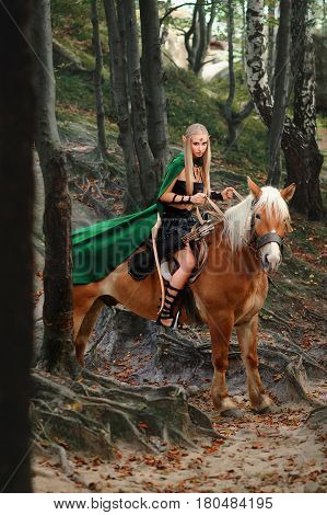 Vertical shot of a beautiful blonde haired female elf archer riding a horse in the forest hunt hunting fearless brave courage Amazonian fighter mythical magical fairy tale costume green cape animal.