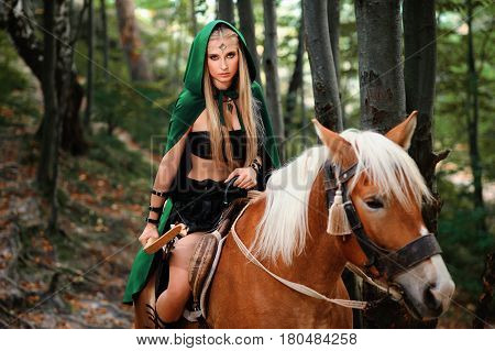 Beautiful sexy female elf warrior looking to the camera confidently sitting on a horse in the woods holding a bow copyspace fighter brave superhero heroic legendary mythical fantasy movie cosplay.