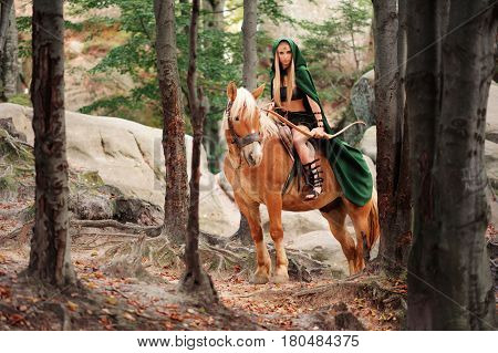 Gorgeous young sexy woman warrior in a red cape riding her horse in the forest copyspace confidence femininity bravery fairy tale Amazonian goddess mythical legendary heroine costume masquerade animal.