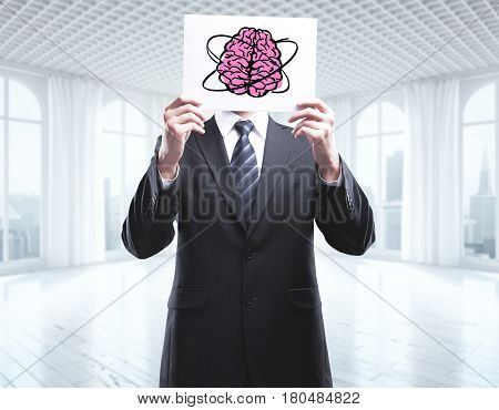 Businessman standing in interior with city view and covering face with pink brain drawn on poster. Brain storm concept. 3D Rendering