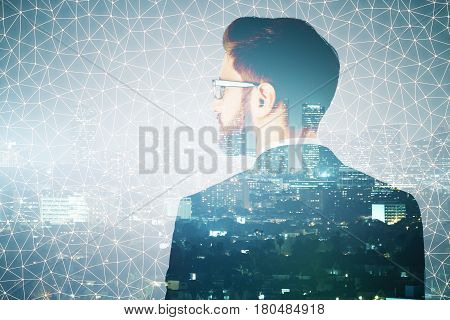 Back view of thoughtful young businessman on abstract polygonal night city background. Future concept. Double exposure