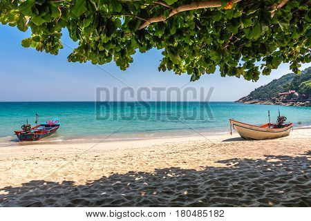 Two motor boats at the tropical beach with white sand. Vibrant blue calm sea and leelawadee tree. Haad Yuan, Phangan, Thailand.