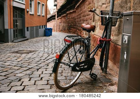 The bike parked next to the pole and secure with locking device on the streets of European cities. Conceptual image of a healthy lifestyle and environmental form of transport.