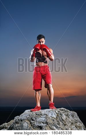 Portrait of a fit young muscular man wearing boxing gloves training outdoors on sunset punching exercising working out preparing competitive motivated determined energetic masculine powerful fighter.
