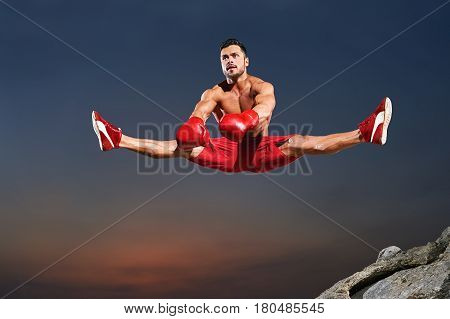 Horizontal shot of a young handsome muscular sportsman doing splits in the air jumping high copyspace gymnast physique sport athletics active lifestyle flexibility stretch fitness motivation endurance.