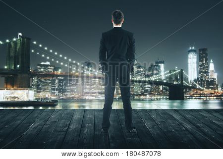 Back view of young man in suit on pier. Night city view background