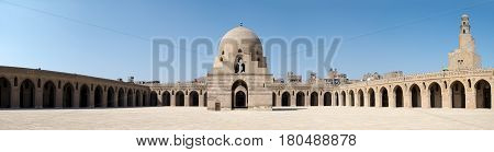 Panorama of the courtyard of Ibn Tulun Mosque Cairo Egypt featuring the ablution fountain and the minaret. The largest one in Cairo and the oldest one in the city with its original form