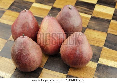 Five organic red pears close-up on a solid wooden inlay chess board background. Several organic red pears grouped together on a beige and brown wood chess board.