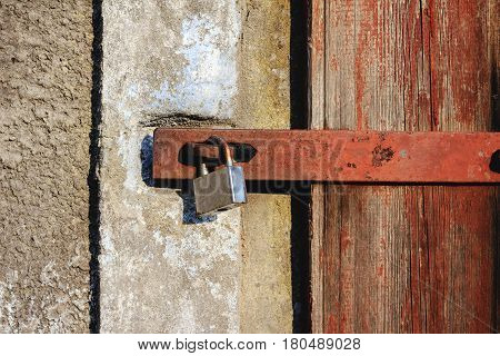 Old lock and red wooden doors with cracks close-up view