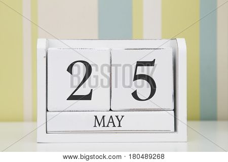 Cube shape calendar for MAY 25 on white table.