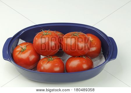 Many hydroponically grown red tomatoes grouped in an oblong blue bowl on a white quartz kitchen counter up close. Several red tomatoes with stems in a blue dish.