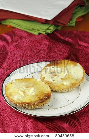 Two halves of a toasted and buttered everything bagel on a round white plate. One everything bagel with seeds and butter served on a round plate.