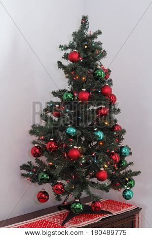 One short artificial Christmas tree decorated with lights and ornament balls. Fake evergreen Christmas tree with ornaments and a variety of LED lights.