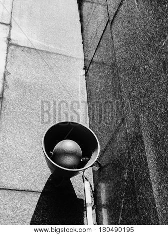 Old metal loudspeakers on marmoreal wall of subway in black and white