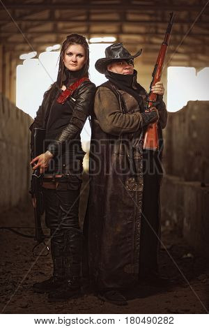 Man with rifle in a leather garment and woman in raider costume with crossbow at post-apocalyptic world.
